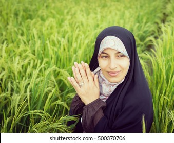 Beautiful happy Muslim woman in green field