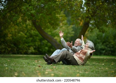 Beautiful happy old people sitting in the autumn park