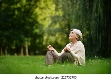Beautiful happy old woman sitting in the autumn park