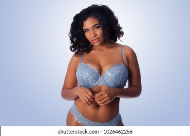 Beautiful happy plus size sexy woman with curly hair in light blue lingerie bra and thong underwear.