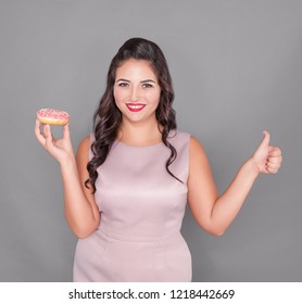 Beautiful happy plus size woman with donut showing thumbs up. Body positive concept