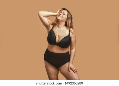 Beautiful and happy plus size woman in black underwear keeping eyes closed and smiling while standing in studio against brown background