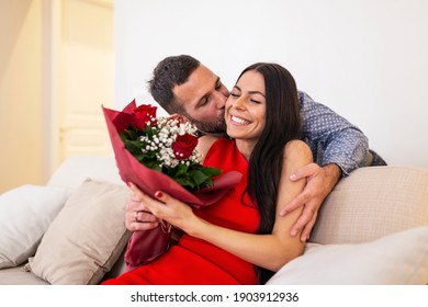 Beautiful, happy, positive couple embracing, holding bouquet of red roses, 14 February happy Valentines day. Handsome man giving flowers to his girlfriend, romantic happy couples on Valentines day