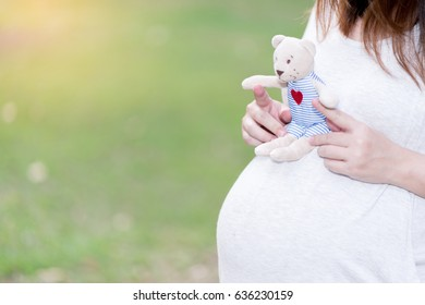 beautiful and happy pregnant asian woman in the garden with doll
