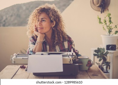 beautiful happy relaxed middle age caucasian woman blonde curly hair taking a break and stop writing with her old typewriter - blogger writer work and hobby time for hipster cheerful modern woman