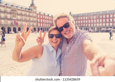 Beautiful happy retired tourist taking a selfie in Plaza Mayor Madrid Spain. In retirement travel around Europe concept.
