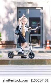 beautiful happy schoolchild with backpack riding scooter and smiling at camera on street
