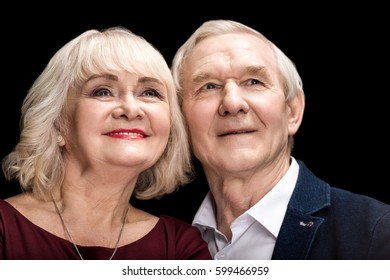Beautiful happy senior couple in love looking away isolated on black