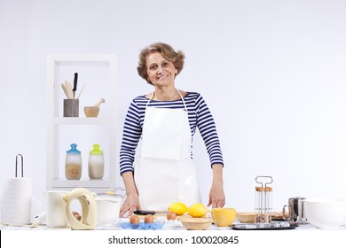 Beautiful and happy senior woman cooking at her kitchen