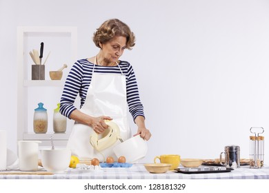 Beautiful and happy senior woman  cooking at her kitchen doing cookies