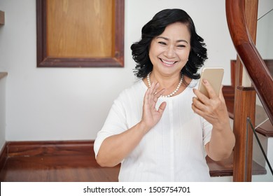Beautiful happy senior woman holding mobile phone in her hand and has online conversation she smiling and waving to somebody