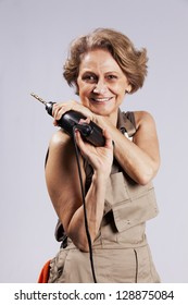 Beautiful and happy senior woman  worker,  posing and holding a drill tool
