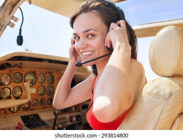 Beautiful happy sexy girl tourist pilot with headset and  in cabin of little plane