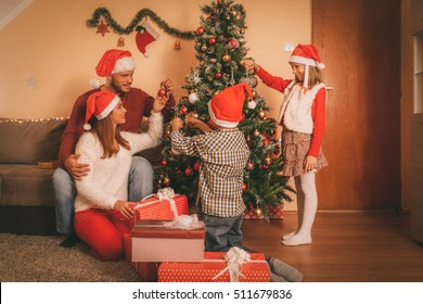 Beautiful happy sister and brother decorating Christmas tree with their parents at the home. They wear Santa hats. Selective focus.