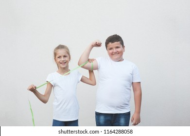 beautiful happy slim caucasian little girl measuring cute thick boy big muscle with tape