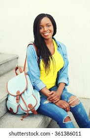 Beautiful happy smiling african woman wearing a jeans shirt with backpack sitting resting on stairs