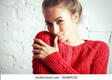 beautiful happy smiling blonde woman girl in warm red sweater. Glamour style portrait