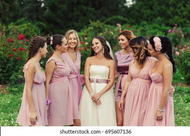 Beautiful happy smiling bride gossip with bridesmaids in light trendy pink dresses on walk outdoors in green summer floral blossom park. Friends, maid of honor, female friendship, wedding concept.