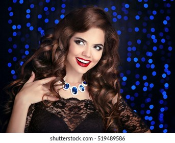 Beautiful happy smiling brunette girl with long shiny curly hair and red lips makeup. Fashion gems jewelry. Glamour girl posing on Christmas party blue lights background.