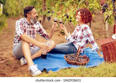 Beautiful happy smiling couple having picnic at a vineyard and toasting with wine for succesfull harvest.