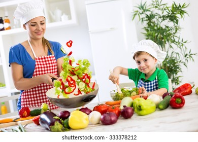 Beautiful happy smiling family cooking vegetables meal at home