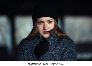 Beautiful happy smiling girl in gray fur coat and black cap. the girl froze in the street. woomen is wrapped in a coat. beautiful girl in black gloves close-up. cold frosty autumn