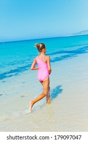 Beautiful happy smiling girl runs along the beach.