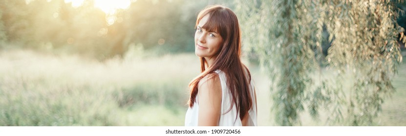 Beautiful happy smiling middle age young Caucasian woman with long dark brown red hair. Casual style real woman female in long white dress outdoor in park nature. Web banner header.
