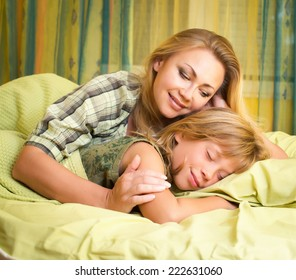 Beautiful happy smiling mother embracing her cute daughter sleeping in bed.