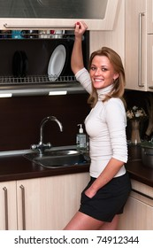 Beautiful happy smiling woman in kitchen interior. One person only
