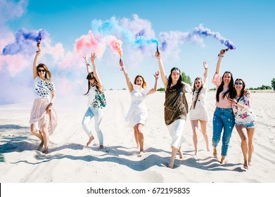 Beautiful happy stylish sexy young girls stand beach and hold light up colored smoke bombs. burn up. Sincere smiles. Party in Style boho. Maiden evening Hen-parties. Bachelorette. Close up. Portrait