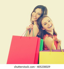beautiful happy teen girls with colored shopping sale bags over white. The best therapy is shopping.