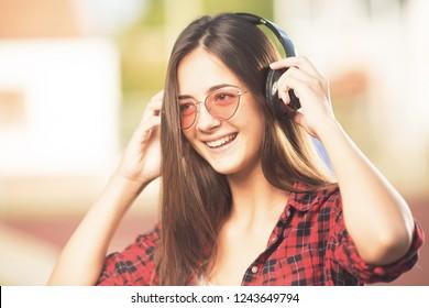 Beautiful happy teenage girl listening to music