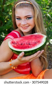Beautiful happy teenager girl eating watermelon outdoors