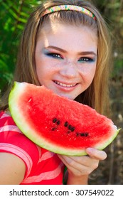 Beautiful happy teenager girl with fashion makeup is eating watermelon outdoors