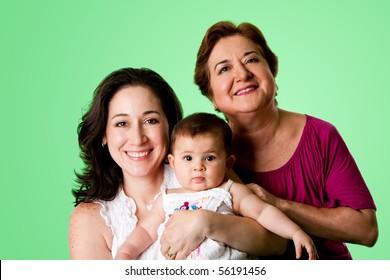 Beautiful happy three 3 generations of Caucasian Hispanic Latina women, grandmother, mother and baby girl, on green.