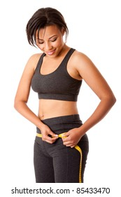 Beautiful happy toned woman weight conscious measuring her size shape around waist hips dressed sporty in grey, isolated.