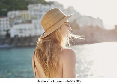 Beautiful happy tourist girl enjoying scenic view of Amalfi Coast on summer adventure vacation