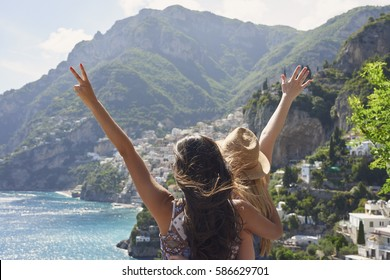 Beautiful happy tourist girl friends enjoying scenic view of Amalfi Coast on summer adventure vacation