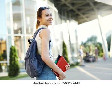 Beautiful happy woman with a backpack going to college. Young female university student with books in campus.