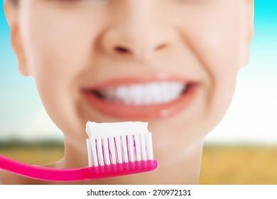 Beautiful happy woman brushing teeth.