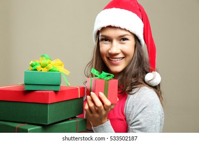 Beautiful happy woman with Christmas gifts on color background