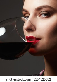 Beautiful happy woman drinking wine. beauty red lips make-up girl with wineglass