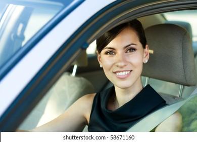 Beautiful happy woman driving her car
