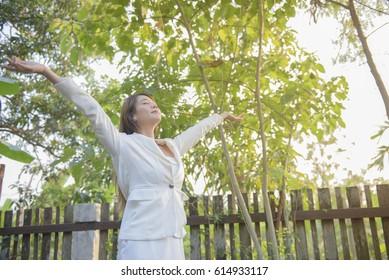Beautiful happy woman enjoying nature outdoor under sunlight of sunset,lifestyle concept.