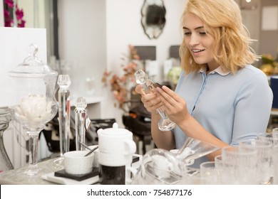 Beautiful happy woman examining price tag of an item at the housewares store. Attractive female customer smiling looking at the price tag happily shopping glassware interior design home sale discount