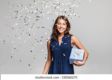 Beautiful happy woman with gift box at celebration party with confetti falling everywhere on her. Birthday or New Year eve celebrating concept