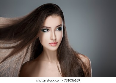 Beautiful happy woman with gorgeous shiny long flying hair. Care of hair