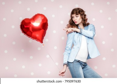 beautiful happy woman with heart shaped air balloons on pink background. St. Valentine's Day.