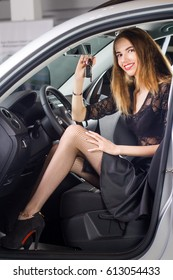 Beautiful, happy woman holding the keys to her new car in her hand